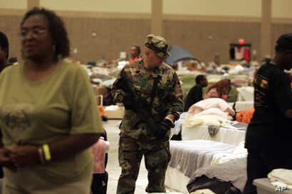 FILE - After Hurricane Katrina, an armed National Guard soldier patrols a Red Cross shelter in Baton Rouge, La., Oct. 4, 2005.