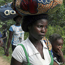 Refugees from Ivory Coast walk with their their belongings through Grand Gedeh county in eastern Liberia Mar 23 2011