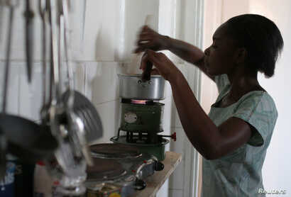 A Tanzanian woman uses a kerosene stove to prepare a meal in the capital Dar es Salaam, Sept. 28, 2006.