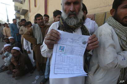 An Afghan refugee who fled his country due to war and famine shows his registration in Peshawar, Pakistan, Oct. 25, 2017.