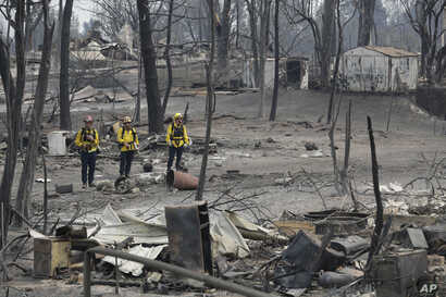 San Bernardino County Fire department firefighters assess the damage to a neighborhood in the aftermath of a wildfire,  July 29, 2018, in Keswick, California.