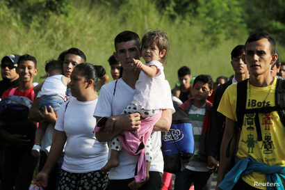 A man carries a child along with other Hondurans fleeing poverty and violence and heading toward the United States, in San Pedro Sula, Honduras, Oct. 13, 2018.
