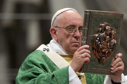 Pope Francis raises the book of the Gospels as he celebrates the opening Mass of the Synod of bishops, in St. Peter's Basilica at the Vatican, Oct. 4, 2015.