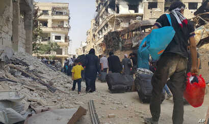 Syrian citizens carry their belonging as they prepare to evacuate from Daraya, a blockaded Damascus suburb, Friday, Aug. 26, 2016. The development in the Daraya suburb is part of an agreement struck between the rebels and the government of President ...