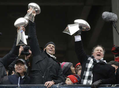 New England Patriots quarterback Tom Brady holds up Super Bowl trophies along with head coach Bill Belichick, right, and team owner Robert Kraft, left, during a rally in Boston, to celebrate the team's Super Bowl 51 win, Feb. 7, 2017.