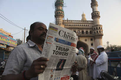 "An Indian man reads a newspaper near the Charming monument that has the headline ""Trump Towers "" to refer to U.S President-elect Donald Trump's victory in Hyderabad, India, Thursday, Nov. 10, 2016."