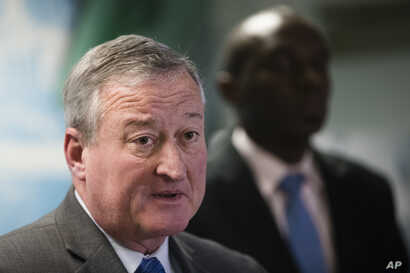 Philadelphia Mayor Jim Kenney, left, accompanied by City Solicitor Sozi Pedro Tulante, speaks during a news conference in Philadelphia, Nov. 15, 2017. A federal judge  Wednesday blocked the U.S. government from withholding a major grant that pays for