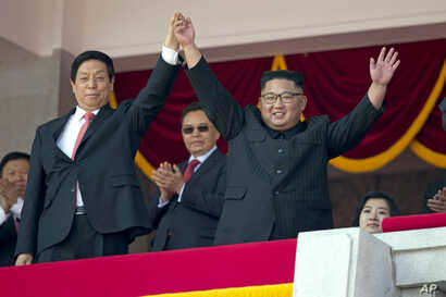 North Korean leader Kim Jong Un, right,  raises hands with China's third highest ranking official, Li Zhanshu, during a parade for the 70th anniversary of North Korea's founding day in Pyongyang, North Korea, Sept. 9, 2018.