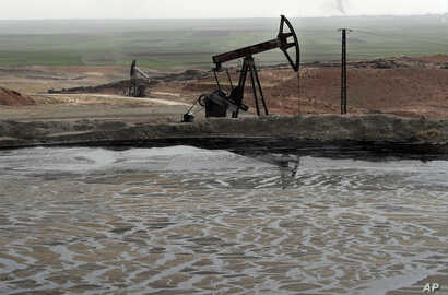 A pond of oil at an oil field controlled by a U.S-backed Kurdish group is seen in Rmeilan, Hassakeh province, Syria, March 27, 2018.