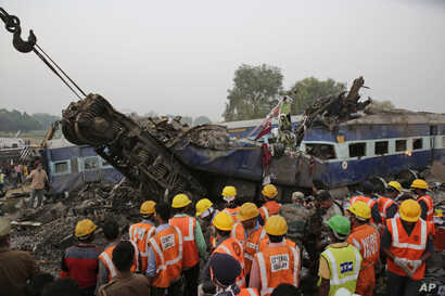 Rescuers search through debris after 14 cars of an overnight passenger train rolled off the track near Pukhrayan village Kanpur Dehat district, Uttar Pradesh state, India, Nov. 20, 2016.