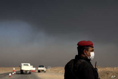 Mideast IraqA member of the Iraqi special forces guards a checkpoint near Awsaja, Iraq, as smoke from fires lit by IS militants at oil wells and a sulfur plant fill the air, Oct. 22, 2016. There are worries coalition forces would be ill-prepared for ...