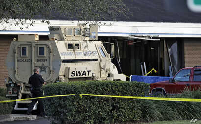 A Sebring, Florida, police officer stands near a Highlands County Sheriff's SWAT vehicle that is stationed in front of a SunTrust Bank branch, Jan. 23, 2019.