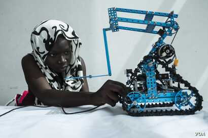 Rokyaha Cisse, 17, from  Dakar, adjusts her team's robot at the 2017 Pan-African Robotics Competition in Dakar, Senegal, May 19, 2017. Their robot sends sounds into the ground, which detect the presence of metal. (R. Shryock/VOA)