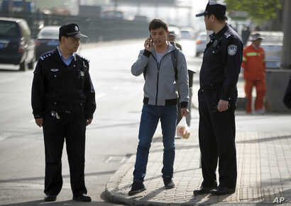 Chinese policemen watch as a man walks near the Beijing No. 3 Intermediate Court in Beijing, April 17, 2015, during the trial of a journalist.