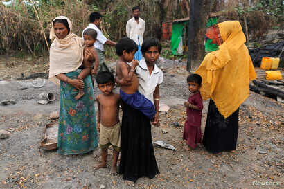 A family stands beside remains of a market which was set on fire, in Rohingya village outside Maungdaw, in Rakhine state, Myanmar, Oct. 27, 2016.