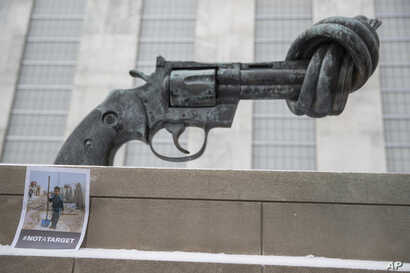 """A photo of a Syrian child is placed next to """"Non-Violence"""" by Swedish artist Carl Fredrik Reutersward, after a moment of silence was observed, March 15, 2017 at United Nations headquarters in New York to mark the 6th anniversary of the Syrian conflic..."""
