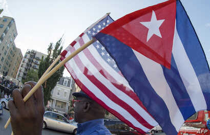 A man waves the US and Cuban flags as he walks in front of the new Cuban Embassy shortly before it's official ceremonial opening July 20, 2015, in Washington, D.C.