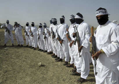 FILE - Taliban suicide bombers stand guard during a gathering of a breakaway Taliban faction, in the border area of Zabul province, Afghanistan.