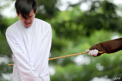 One of two Indonesian men is publicly caned for having sex, in a first for the Muslim-majority country where there are concerns over mounting hostility towards the small gay community, in Banda Aceh on May 23, 2017.