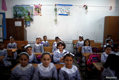 Palestinian schoolgirls sit inside a classroom at an UNRWA-run school, on the first day of a new school year, in Gaza City, Aug. 29, 2018.