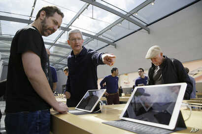 Apple CEO Tim Cook points out the new 9.7 inch iPad Pro to a customer during a visit to the Apple Store, March 31, 2016, in Palo Alto, Calif.