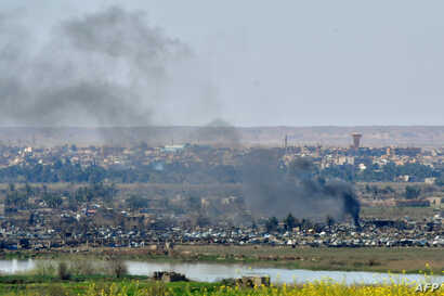Smoke rises from the Islamic State (IS) group's last remaining position in the village of Baghuz during battles with the Syrian Democratic Forces (SDF), in the countryside of the eastern Syrian province of Deir el-Zour, March 20, 2019.