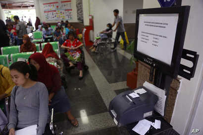 "Patients wait near a queue number dispenser affected by ""WannaCry"" attack at Dharmais Cancer Hospital in Jakarta, Indonesia,  May 15, 2017."