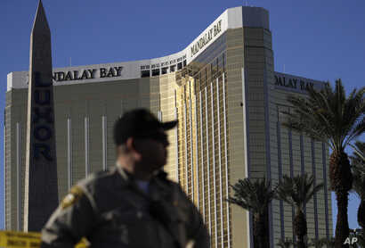 A Las Vegas police officer stands by a blocked-off area near the Mandalay Bay Resort and Casino, Oct. 3, 2017, in Las Vegas, which is near the site of the Oct. 1 mass shooting by Stephen Craig Paddock.