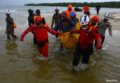 Rescue workers carry a body bag containing the remains of a victim of a tsunami at Tanjung Lesung in Pandeglang, Banten province, Indonesia, Dec. 25, 2018.