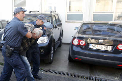FILE - Montenegrin police officers escort a suspect in Podgorica, Oct. 16, 2016. In all, 20 suspects linked to a coup plot aimed at derailing the Balkan nation's bid to join NATO were arrested ahead of Montenegrin elections.