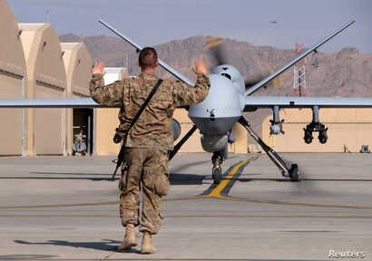 FILE - A U.S. airman guides a U.S. Air Force MQ-9 Reaper drone as it taxis to the runway at Kandahar Airfield, Afghanistan, March 9, 2016.