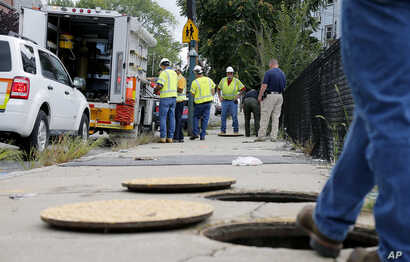 A worker with Columbia gas stands over an open man hole as the crew works to make sure there are no gas leaks at the corner of Parker and Salem Streets in Lawrence, Mass., Sept. 14, 2018.