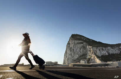 FILE- A woman walks on the Spanish side of the border between Spain and the British overseas territory of Gibraltar with the Rock of Gibraltar in the background, in La Linea de la Concepcion, Spain, March 1, 2017.