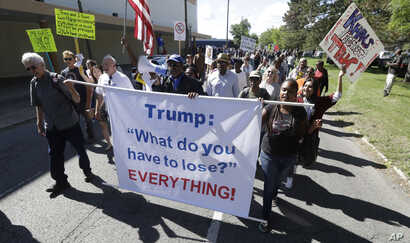 Protesters march outside the Great Faith Ministries International church in Detroit, where Donald Trump visited with the church members, Sept. 3, 2016. Area clergy are denouncing the visit by Trump, who hopes to convince black voters to cast their ba...