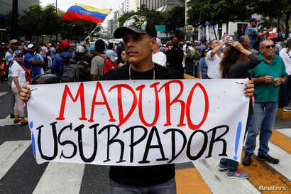 "A man holding a placard that reads ""Maduro usurper"" takes part in a gathering with members of the Venezuelan National Assembly in Caracas, Venezuela, Jan. 11, 2019."