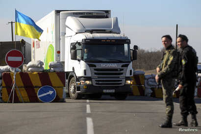 Ukrainian servicemen stand guard at a checkpoint near the town of Armyansk in Kherson region adjacent to Crimea, March 23, 2014.