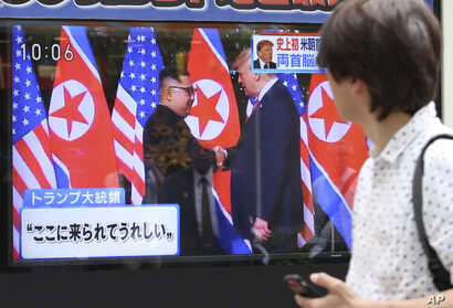 "A man looks at a TV screen showing North Korean leader Kim Jong Un, left, and U.S. President Donald Trump shaking hands before their meeting in Singapore, in Tokyo, June 12, 2018. Japanese letters read: ""Happy to come here."""