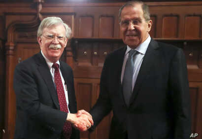 U.S. National Security Adviser John Bolton, left, and Russian Foreign Minister Sergey Lavrov shake hands prior to their talks in Moscow, Oct. 22, 2018.