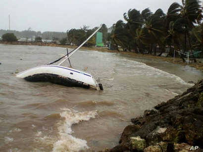 A boat lays on its side off the shore of Sainte-Anne on the French Caribbean island of Guadeloupe, early Sept. 19, 2017, after the passing of Hurricane Maria.