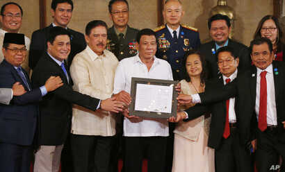 """FILE - President Rodrigo Duterte, center, and leaders of the Moro Islamic Liberation Front, including Al Haj Murad Ebrahim, left, Mohagher Iqbal, right, and Ghadzali Jaafar, second from right, hold together the signed """"Organic Law for the Bangsamoro"""
