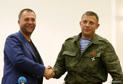 "Aleksander Borodai (L), leader of the self-proclaimed ""Donetsk People's Republic"" shakes hands with rebel leader Aleksander Zakharchenko, during their news conference in Donetsk, August 7, 2014."