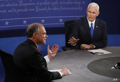 Republican vice-presidential nominee Gov. Mike Pence, right, speaks as Democratic vice-presidential nominee Sen. Tim Kaine listens during the vice-presidential debate.