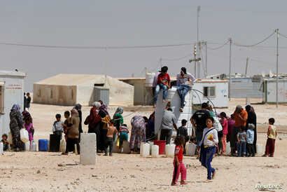 Syrian refugees collect water at the Al-Zaatari refugee camp in Mafraq, Jordan, near the border with Syria, August 18, 2016.