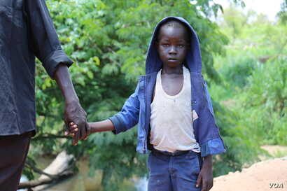 Seven year-old John Wesley slowly crosses the border from South Sudan into Uganda with his father at the Busia border point on  April 1 in Koboko, Uganda.
