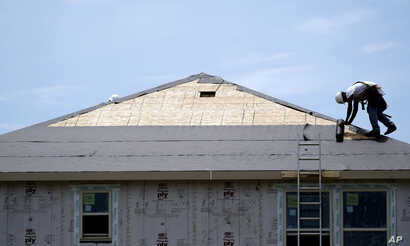 FILE -- A construction worker puts down roofing paper on a new home in Houston. Texas was a popular destination for new home buyers in 2018.