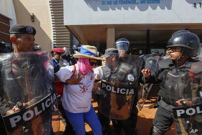 "A masked anti-government protester is arrested by police as security forces disrupt an opposition march, coined ""United for Freedom,"" in Managua, Nicaragua, Sunday, Oct. 14, 2018."