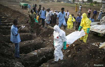Health workers carry the body of an Ebola victim for burial at a cemetery in Freetown, December 17, 2014.  The death toll in the Ebola epidemic has risen to 6,915 out of 18,603 cases as of Dec. 14, the World Health Organization (WHO) said on Wednesda...