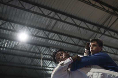 In this May 27, 2016 photo, Popole Misenga, a refugee from the Democratic Republic of Congo, left, practices judo in hopes of making the cut for an Olympic team of refugee athletes, at the Reacao Institute in Rio de Janeiro, Brazil.