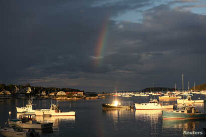A rainbow is seen above lobster boats in the harbor of Stonington, Maine, July 4, 2017.