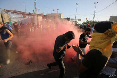 """Supporters of Iraqi cleric Moqtada al-Sadr flee the tear gas fired by security forces during clashes after demonstrators broke into Baghdad's fortified """"Green Zone"""" on May 20, 2016."""